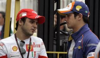Ferrari's Formula One driver Massa of Brazil chats with his compatriot, Renault driver Piquet Junior, at the pit-lane in Sao Paulo